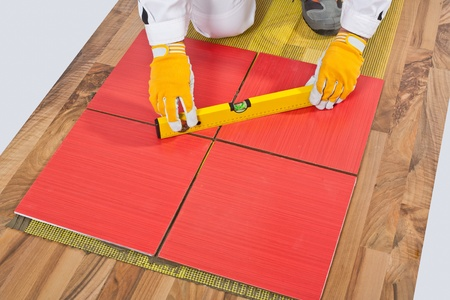 Worker levels Tiles applied on old wooden Floor reinforced net Stock Photo - 14669967