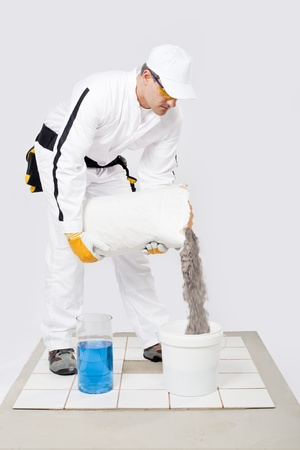 Worker mix tile adhesive in a bucket of water  photo
