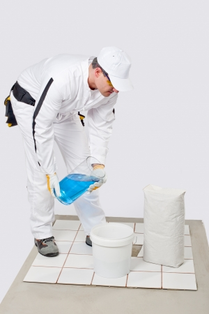 Worker add water to mix tile adhesive in bucket to glue broken white tile on floor