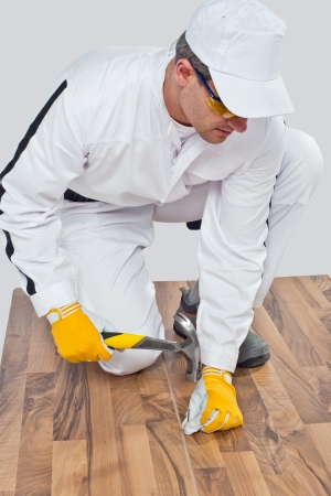 Worker nailed a nail with a hammer on the wooden floor Stock Photo