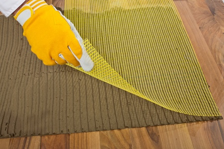 tile adhesive: worker puts the reinforced fiber mesh on an old wooden floor