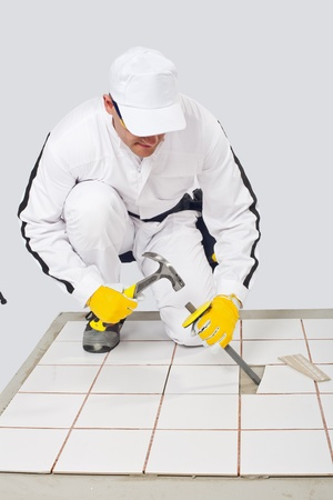 Worker removes old white tiles from floor with hammer