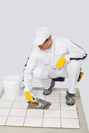 tile adhesive: Worker repairs old white tiles with tile adhesive and trowel Stock Photo