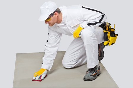 worker cleans with sand paper cement substrate to remove spots photo