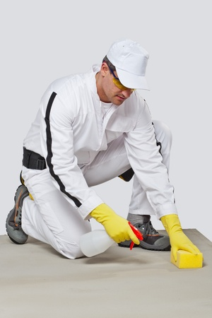 worker in white working overalls use sponge and spray to clean cement substrate photo