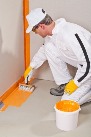 worker with brush applying waterproofing around the wall and floor  Stock Photo