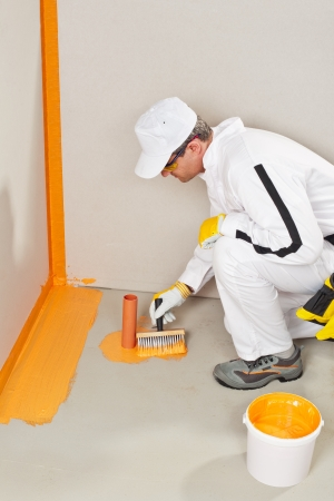 worker waterproofing around the wall, floor and siphon photo