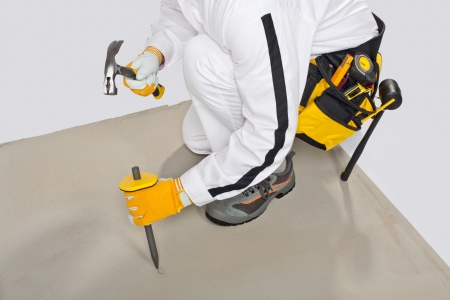 Worker with chisel and hammer check concrete base before tilling