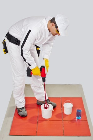 tile adhesive: worker with electric drill mixer tile adhesive on bucket