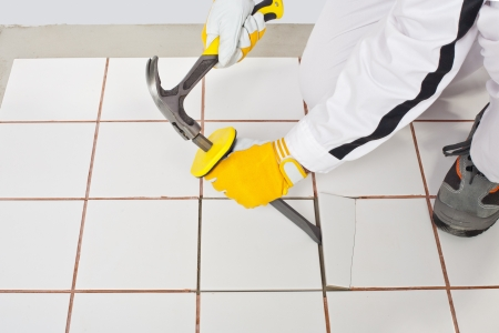 construction worker with a hammer and chisel remove the old broken ceramic tile on bathroom floor before tilling