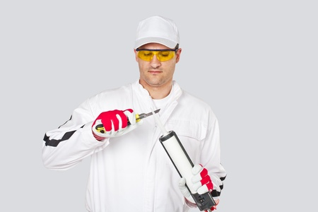 Worker with knife remove cuts cap sealant silicon gun Stock Photo