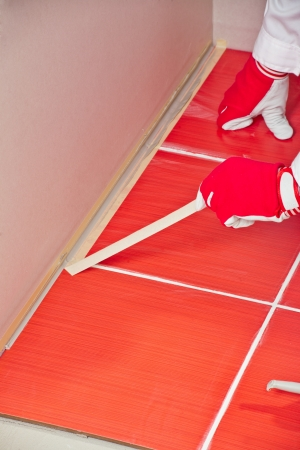 worker with masking type applying silicone sealant between wall and floor Stock Photo