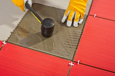 Worker with rubber hammer install glass tiles with tile adhesive checking Stock Photo - 14669994