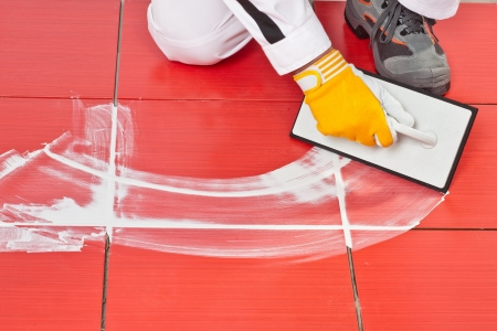 worker with rubber trowel applying white grout tile on red floor tilles Stock Photo