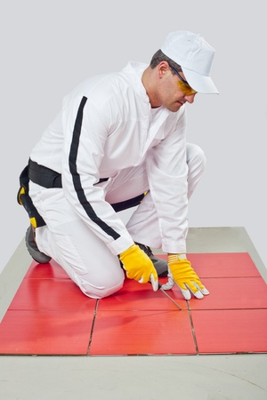 tile adhesive: Worker with Sharp tool clean spaces between tiles remove tile adhesive debris dust particles Stock Photo