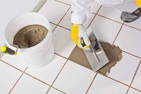 Trowel and old white tiles with tile adhesive bucket  Repaired old tile and preparation for new tiles