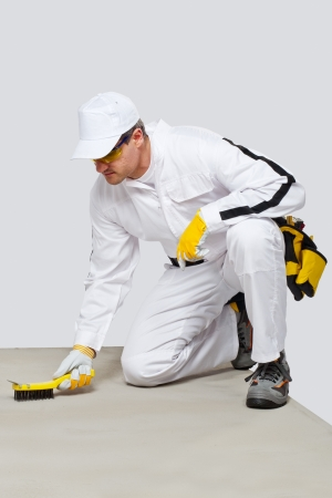 substrate: Kneeling Worker with wire brush cleans the cement substrate floor before tilling