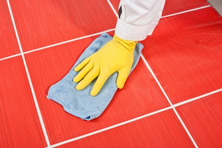 Worker with yellow gloves and blue towel cleans red tiles grout photo