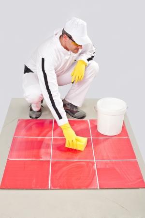Travailleur avec des gants jaunes et éponge jaune rouge nettoie coulis carreaux à partir de poussière de ciment
