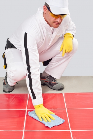 Worker with yellow gloves and blue towel cleans red tiles grout from cement dust photo