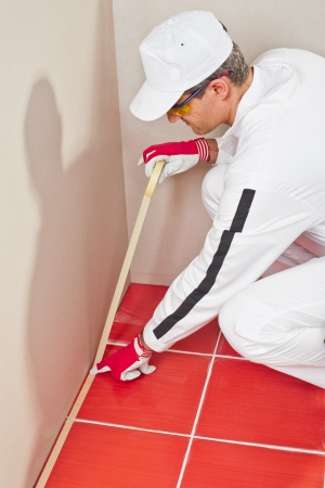 Worker with white overalls wrapped with masking tape to protect red tiles from silicone sealant on corner