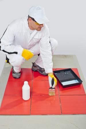 cartilla: trabajador de la construcci�n con un pincel en la mano manchada de las juntas de las baldosas con cartilla de sellado