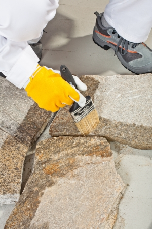 worker brush primer grout of stones joint