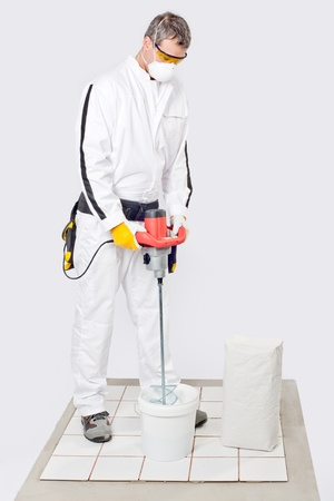 dust mask: Worker Mix Tile Adhesive With Machine Tool