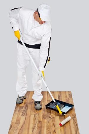 cartilla: trabajador con pintura de imprimaci�n piso de madera para la impermeabilizaci�n