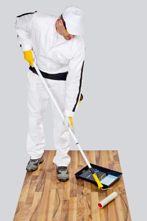 Worker Paint With Primer Wooden Floor For Waterproofing Stock Photo