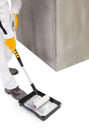 priming paint: Worker priming with a paint roller Stock Photo