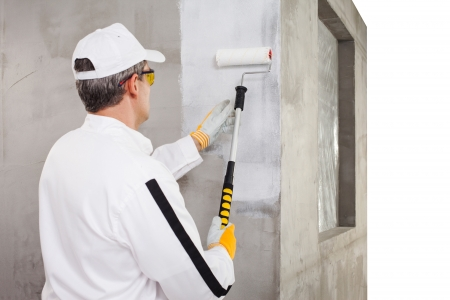 Worker priming with a paint roller Stock Photo