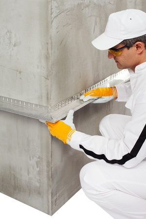 wall angle corner: Worker fixing a lath on a corner