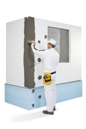 Worker coating a corner-lath with a putty photo