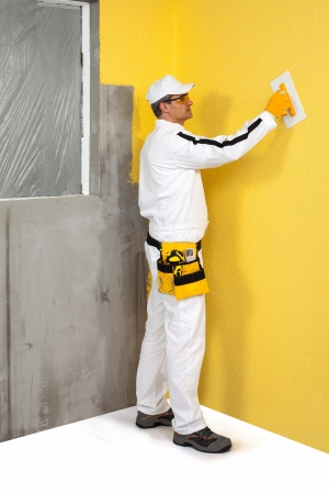 gypsum: Worker spreading a plaster on a wall
