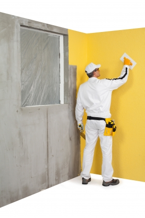 parget: Worker spreading a plaster on a wall