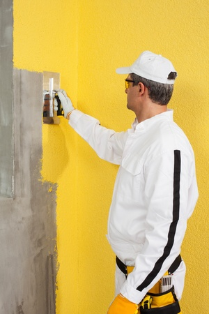 Worker spreading a plaster on a corner-wall photo