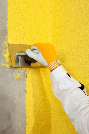 A trowel spreading a plaster on a corner-wall photo