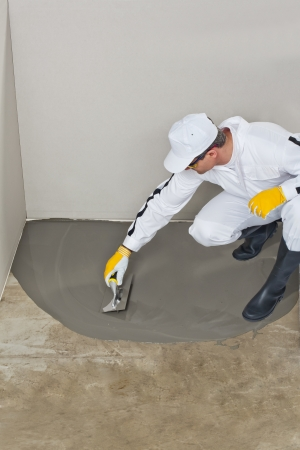 Worker spreading self leveling compound with trowel photo