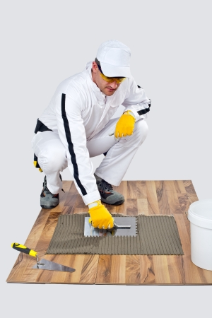 construction worker applyes tile adhesive on wooden floor photo