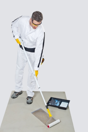 worker with paint roller primed cement floor before tilling photo