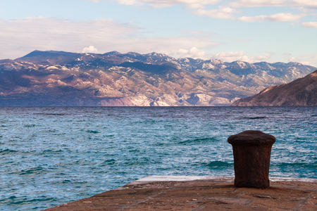 the mainland: A pier in Baska, Krk, Croatia with the Croatian mainland mountains in the background