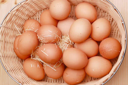 Macro shoot of brown eggs at hay nest in chicken farm photo