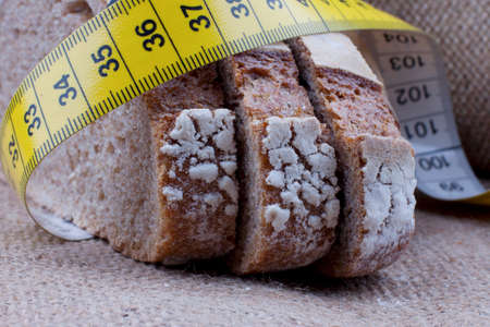Dieting concept. Tape measure wrapped around slices of bread Banque d'images