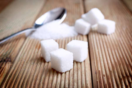 Sugar cubes and white sugar with spoon.