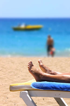 longue: Young woman relaxing in chaise longue on the beach Stock Photo