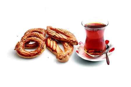 Turkish flour products and a cup of black tea on a white background