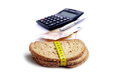 EURO currency with financial calculator and brown slice of breads with measuring tape isolated on white background Stock Photo