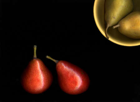 Fresh organic pears in a bowl isolated on black background