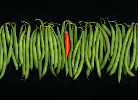 Organic string beans and single red hot chili pepper isolated on black background